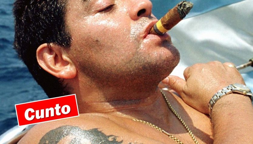 Diego Maradono, smoking a large cigar on a boat